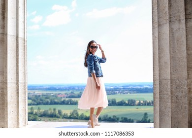 Happy woman wearing jeans jacket ,pink skirt and sneaker she standing and smiling at camera enjoying her summer day with beautiful viewpoint in European city.