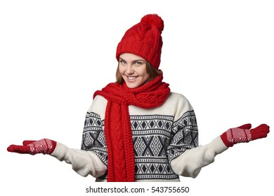 Happy woman wearing knitted warm scarf and hat holding blank copy spaces on both open hand palms, looking at camera, over white background