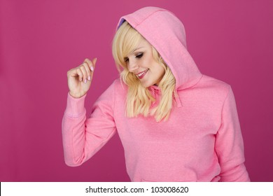 Happy woman wearing a pink sports hoodie on a pink background.  Woman in pink.
