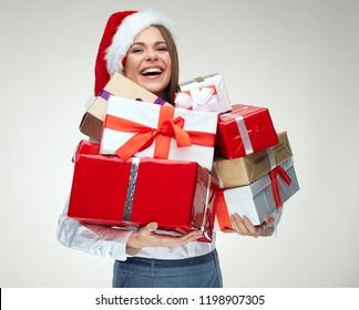 Happy woman wearing santa hat holding pile of gifts. Positive emotional Santa girl.