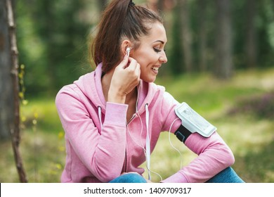Happy woman, wearing sportswear, is sitting on the ground and, listening music in a break of exercises in a sunny forest.