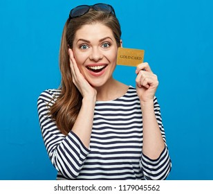 Happy woman wearing striped shirt holding credit card. Girl with long hair isolated portrait on blue.