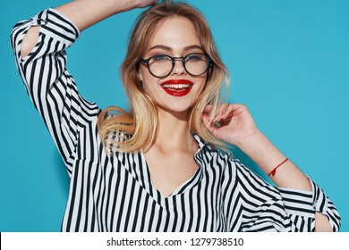 A happy woman was wearing a striped shirt smiling at the camera with glasses on her face