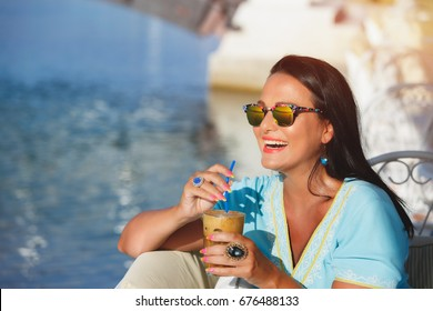 Happy woman wearing sunglasses, holding glass of iced coffee and looking away smiling, selective focus, vintage toned image