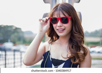 Happy woman wearing sunglasses posing with shopping bags and looking at camera, shopping concept