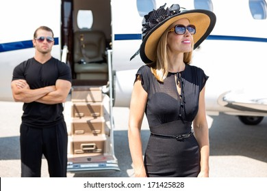 Happy woman wearing sunhat and sunglasses with bodyguard and private jet in background