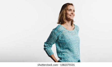 Happy woman wearing a woollen top standing against white background. Smiling woman with short brown hair looking away.
