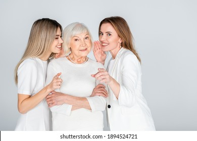 happy woman whispering in ear of senior mother near young daughter isolated on grey