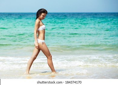 Happy woman in white bikini swimwear walking on a beach. Vacation, beautiful sea and natural. Tan girl in summer. Perfect body shapes, relaxing soul