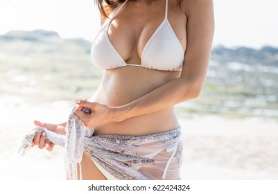 Happy woman in white bikini tried to covered with piece of fabric