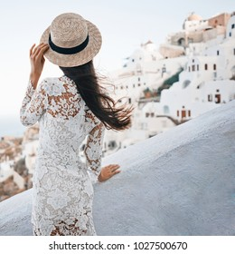 Happy woman in white dress and straw hat enjoying her holidays on Santorini island. View on Aegean sea from Oia. Europe summer travel destination. Greek Islands