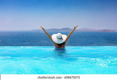 Happy woman with white hat enjoys her vacation in the pool