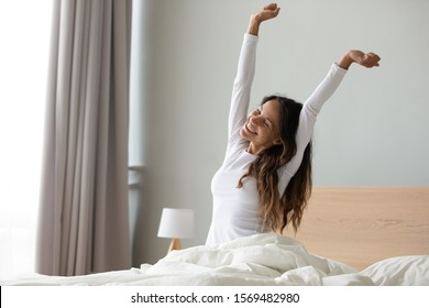 Happy woman in white nightwear sitting in bed awakened from enough and healthy sleep feels good, stretching her arms muscles after sleep and long immobility wakes up start new day with smile concept