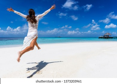 Happy woman in white summer dress jumps of excitement on a tropical beach and enjoys her holidays
