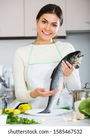 Happy woman in white sweater with fresh salmon fish