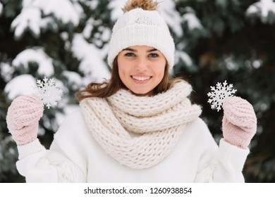 Happy woman in white winter clothes holding a beautiful snowflake in a park. Happy winter concept
