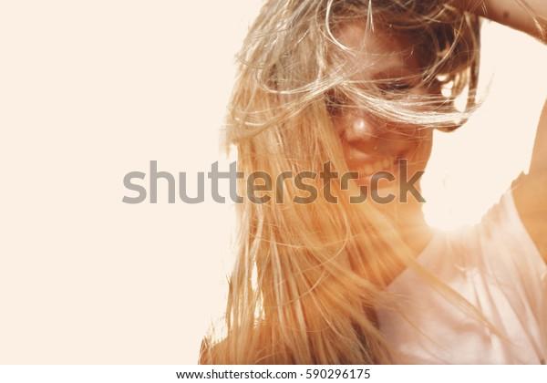 Gelukkige vrouw met winderig rommelig haar backlit door zon selectieve focus ingekleurd beeld, kopieer ruimte.