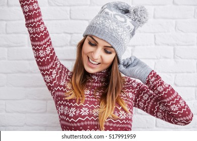 Happy woman in winter clothes raising hand