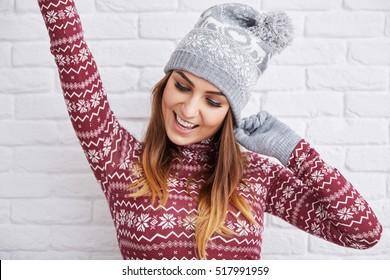 Schöne Frau im Winter beim Handheben von Kleidung