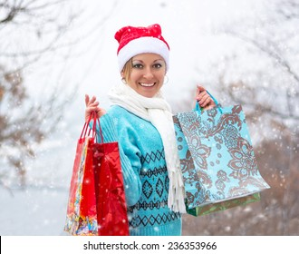 Happy woman in winter clothes with shopping bags before Christmas