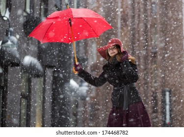 Happy woman at winter day with red umbrella