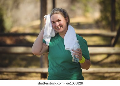 Happy woman wiping sweat with towel after workout in boot camp