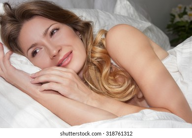 Happy Woman Woke up in the Morning with a Smile on her Face. Close Portrait of a Beautiful Girl lying in her Bed, her arms wrapped around the Pillow, her Face gentle smile.