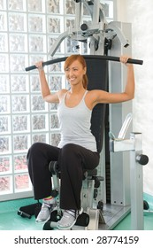 Happy woman working out arms' muscles on exercise machine.