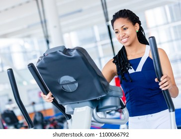 Happy woman working out at the gym on an elliptical