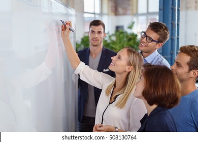 Happy woman writing on blank white board with fellow staff members standing around smiling
