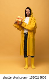 happy woman in yellow raincoat and wellies holding gift box on yellow background