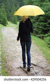 Happy Woman with yellow umbrella walking in forest under the rain. Happiness, positivity concept