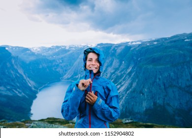 Happy woman zip up blue sportive jacket before rain, relaxing and smiling in cliff during trip Norway. Trolltunga hiking route
