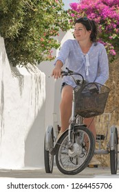 Happy woman's portrait on a bicycle at summer vacations at Andros island in Greece.
