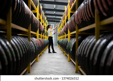 Happy women is checking the stock of tires at the warehouse for tire inspection to check the balance of the product.