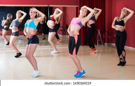Happy women are dancing modern jazz in gym.
