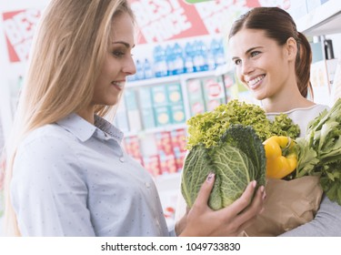 Happy women doing grocery shopping together at the supermarket, they are holding fresh organic vegetables