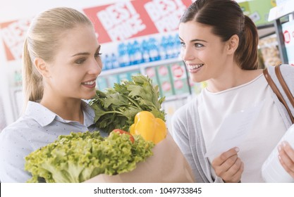 Happy women doing grocery shopping together at the supermarket, they are holding a grocery bag filled with fresh vegetables and a shopping list