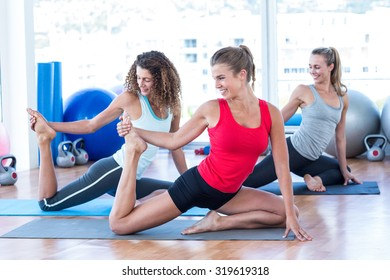 Happy women doing pigeon pose with one hand right leg grab in fitness studio