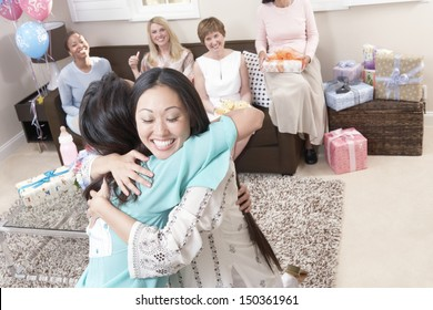 Happy women embracing with friends in background at baby shower