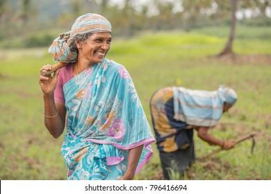 Happy women farmer working on farm field in Tamilnadu.