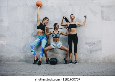 Happy women in fitness clothes having fun standing outdoors with basketball skipping rope and medicine ball.