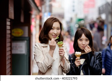 Happy women friends eating ice cream on travel in Japan