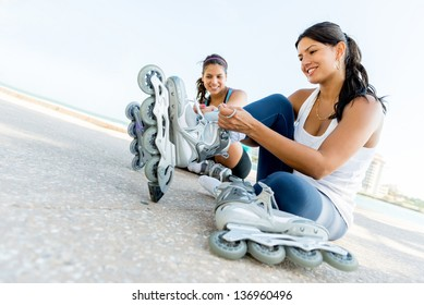Happy women getting ready for skating outdoors