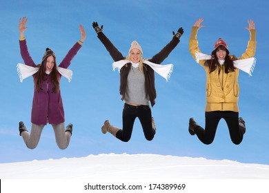 Happy women with gloves, scarf and caps jumping in winter