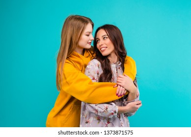 Happy women holding each other isolated over turquoise blue background