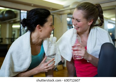 Happy women holding water bottle while relaxing after workout in gym