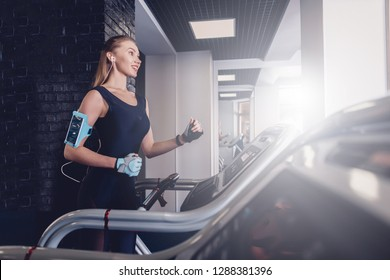 Happy women jogging on a treadmill. Training on cardio to maintain good health. Comfortable clothing for training in the gym. Sports hall for sports with a trainer. Running for good physical condition