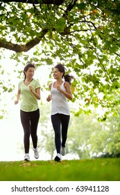 Happy women jogging at the park - fitness concepts