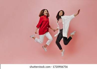 Happy women jump on isolated background. Tanned Asian girls in stylish outfits move on pink backdrop.